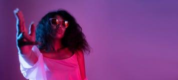 Los vidrios africanos del desgaste de la muchacha de la moda bailan en fondo púrpura del partido de disco fotos de archivo