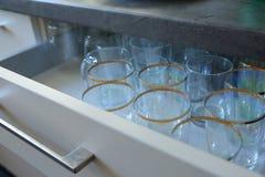 Los vidrios arreglaron en fila en un zapatero con los cajones en la cocina Fotos de archivo libres de regalías