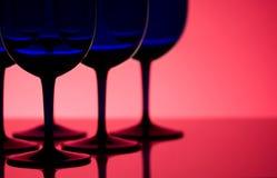 Los vidrios azules apoyan encendido en fondo rojo Foto de archivo