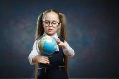 Los vidrios caucásicos del desgaste de la colegiala dan vuelta al globo del mundo fotografía de archivo libre de regalías