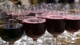 Los vidrios con alcohol y diversas bebidas, el vino y el jugo están en la tabla de buffet en un restaurante metrajes