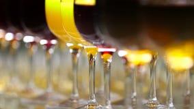 Los vidrios con alcohol y diversas bebidas, el vino y el jugo están en la tabla de buffet en un restaurante almacen de video