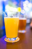 Los vidrios de cerveza en la barra con el bokeh encienden el fondo Foto de archivo