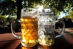 Los vidrios de cerveza en una cerveza bávara cultivan un huerto en Munich Foto de archivo libre de regalías