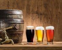 Los vidrios de cerveza y de cerveza inglesa barrel en la tabla de madera Fotos de archivo libres de regalías