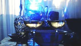 Los vidrios de cristal en una tabla en un restaurante, tabla de banquete, vidrios de vino efectúan la iluminación azul Foto de archivo libre de regalías