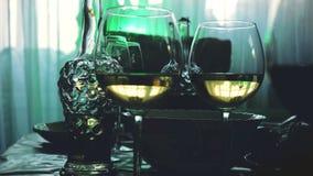 Los vidrios de cristal en una tabla en un restaurante, tabla de banquete, vidrios de vino efectúan la iluminación verde Fotografía de archivo