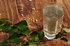 Los vidrios de jugo de la savia del abedul beben ramas del abedul en la nutrición útil de la tabla del fondo de la primavera sana Imagen de archivo