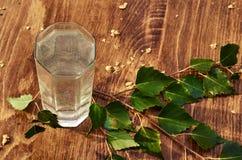 Los vidrios de jugo de la savia del abedul beben ramas del abedul en la nutrición útil de la tabla del fondo de la primavera sana Imágenes de archivo libres de regalías