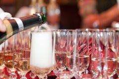 Los vidrios de la botella son champán vertido Foto de archivo libre de regalías