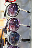 Los vidrios de sol de las gafas de sol empilados reman en la visualización del departamento Foto de archivo libre de regalías
