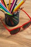 Los vidrios de sol rojos con el manojo de color dibujaron a lápiz en un soporte Fotos de archivo libres de regalías