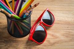 Los vidrios de sol rojos con el manojo de color dibujaron a lápiz en un soporte Imagen de archivo libre de regalías