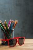 Los vidrios de sol rojos con el manojo de color dibujaron a lápiz en un soporte Fotografía de archivo
