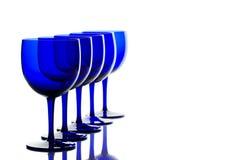 Los vidrios del azul de cobalto apoyan encendido en el fondo blanco Foto de archivo