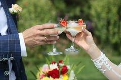 Los vidrios del champán en las manos de los recienes casados Imagen de archivo