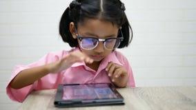 Los vidrios del desgaste de la niña están jugando teblet almacen de metraje de vídeo