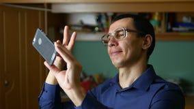 Los vidrios del hombre hacen un smartphone divertido del teléfono del selfie interior almacen de metraje de vídeo