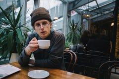 Los vidrios del hombre joven para la visión y la camisa sirven el café de consumición en un café en tiempo libre Fotos de archivo