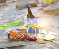 Los vidrios del vino blanco en la playa meriendan en el campo Foto de archivo