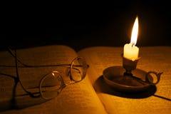 Los vidrios del vintage en una biblia se encendieron por luz de una vela Foto de archivo