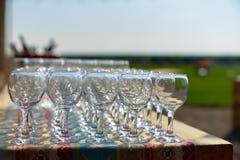 Los vidrios hermosos de la tabla del día de fiesta de filas del glassestwo del vino de vidrios en una tabla con los tableclothgla Imagen de archivo
