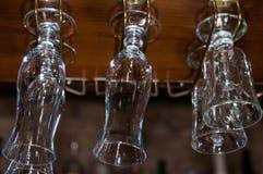 Los vidrios limpios vacíos cuelgan sobre barra de madera imágenes de archivo libres de regalías