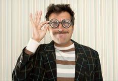 Los vidrios miopes locos tontos del empollón sirven gesto divertido Foto de archivo