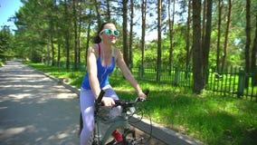Los vidrios que llevan deportivos hermosos de la mujer joven con los auriculares montan su bici de la manera feliz y positiva en  almacen de metraje de vídeo
