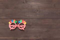 Los vidrios rosados con masaje del feliz cumpleaños están en el backgr de madera Imágenes de archivo libres de regalías