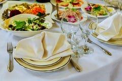 Los vidrios vacíos fijaron con la servilleta in fine que cenaba el restaurante adornado Fotografía de archivo libre de regalías