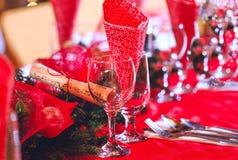 Los vidrios vacíos fijaron en comedor con la decoración roja del día de fiesta Fotos de archivo