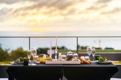Los vidrios vacíos fijaron en el restaurante - tabla de cena al aire libre en la puesta del sol Fotos de archivo libres de regalías