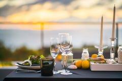 Los vidrios vacíos fijaron en el restaurante - tabla de cena al aire libre en la puesta del sol Foto de archivo