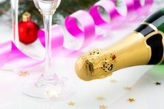 Los vidrios y la botella de champán, serpentean aislado en un fondo blanco. Foto de archivo