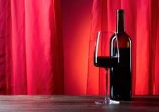 Los vidrios y la botella de rede wine en un fondo rojo Foto de archivo libre de regalías