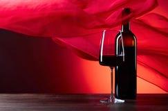 Los vidrios y la botella de rede wine en un fondo rojo F escarpada roja Imagen de archivo