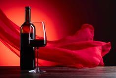 Los vidrios y la botella de rede wine en un fondo rojo F escarpada roja Fotos de archivo