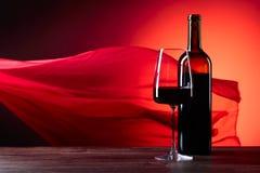 Los vidrios y la botella de rede wine en un fondo rojo F escarpada roja Foto de archivo