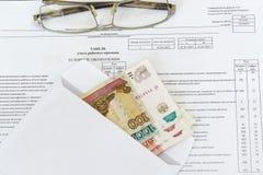 Los vidrios y un sobre con los billetes de banco de la rublo 100, 1000, 5000 están en la hoja de la contabilidad de la hora labor Imagen de archivo
