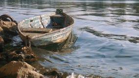 Los viejos giros excéntricos amarrados del barco golpearon por las ondas en un río almacen de video
