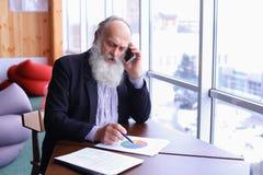 Los viejos hombres jubilados llaman para partner con el teléfono elegante usando nuevo techn fotografía de archivo