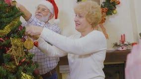Los viejos pares felices adornan el árbol de navidad juntos metrajes