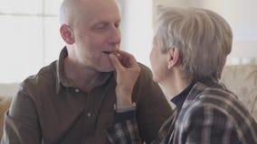 Los viejos pares mayores sentar el togeher en el sofá, mujer con el pelo corto gris pusieron el caramelo de chocolate en la boca  metrajes
