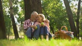 Los viejos pares sanos alegres que se relajan en hierba, sosteniendo manzanas y abrazando, meriendan en el campo