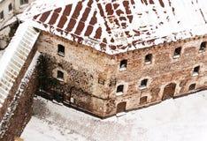 Los viejos soportes de piedra medievales de la fortaleza cubiertos con nieve imagenes de archivo