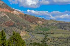 Los vientos del camino a lo largo de la base de la cordillera enorme en Wyoming septentrional imagen de archivo libre de regalías