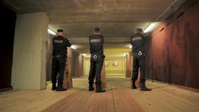 Los vigilantes de seguridad llevan las pistolas de los bolsillos el fuego en galería de tiroteo almacen de metraje de vídeo