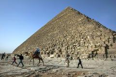 Los visitantes a bordo de un camello montan más allá de la gran pirámide de Khufu en Giza en El Cairo, Egipto Imágenes de archivo libres de regalías