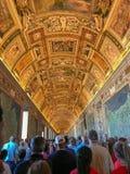 Los visitantes caminan pacientemente a través de pasillos del museo del Vaticano debajo de IL fotos de archivo